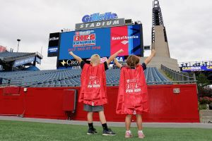 Foxborough residents Dexter Griffin, left, and Cate Marchi, show off the superhero capes that children participating in this year's Harvard Pilgrim Finish at the 50 Kids Fun Run will receive. Gillette Stadium and Patriot Place will host the ninth annual Finish at the 50 road races on July 3.