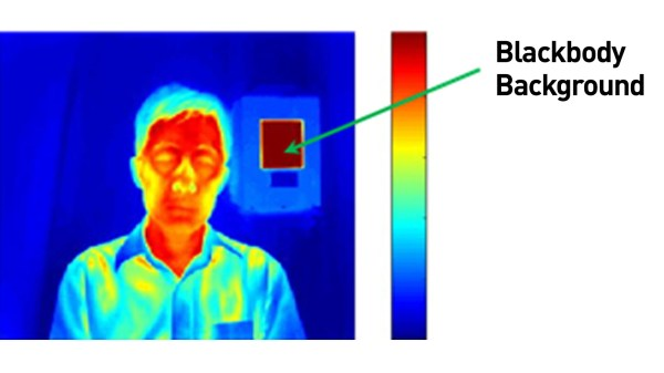 Picture of the infrared thermal image of a man standing in front of a plain wall with a small square blackbody background on the wall. His face is shown in a dark red color indicating a higher skin surface temperature than his clothing that is shown in blue and yellow. The blackbody background is shown in very dark brown indicating minimized reflection of infrared radiation. A temperature range scale bar to the right of the picture shows a color range from dark brown through the color spectrum to dark blue.