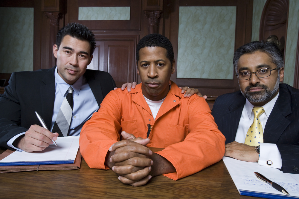 Criminal And Advocates Sitting In Courtroom