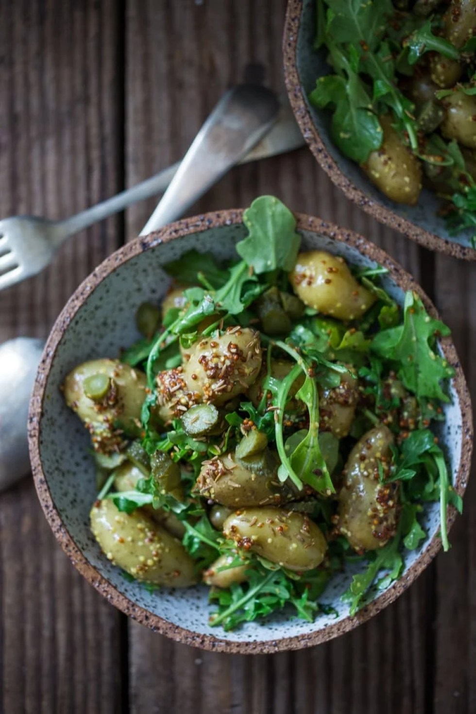 12 Delicious Spring Recipes to celebrate the season!  A healthy lightened up Potato Salad with Mustard Seed dressing, cornichons and baby Arugula.   www.feastingathome.com