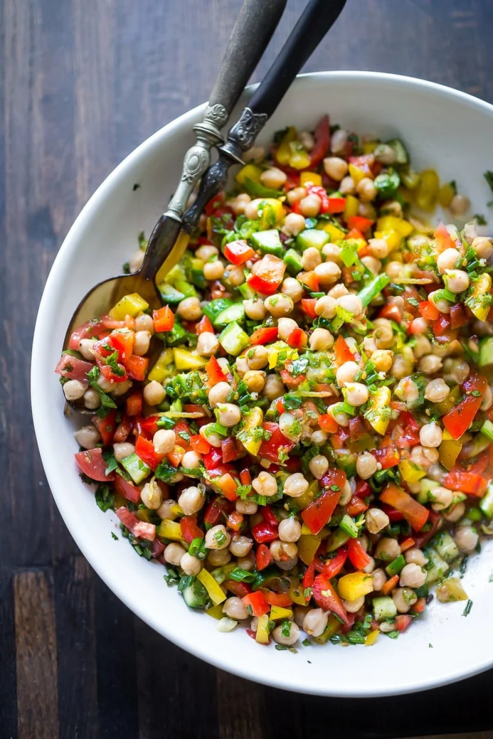 A simple & delicious recipe for Balela Salad, made w/ finely chopped vegetables, chickpeas, fresh herbs, lemon & olive oil. Serve in a pita with tahini sauce or over greens. | www.feastingathome.com