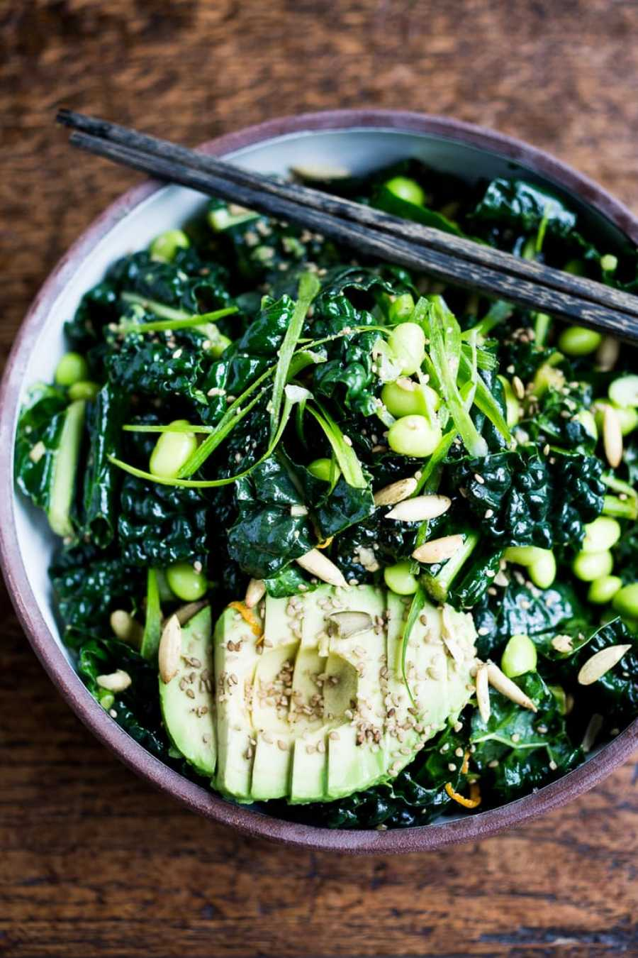 EAT CLEAN with these 20 simple Plant-Based Meals   Emerald Kale Salad w/ Sesame Ginger Dressing, Avocado, edamame, scallions, pumpkin seeds and orange zest. Add seared tofu and turn it into dinner!   www.feastingathome.com #vegan #kale #salad #glutenfree
