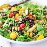 Summer Pasta with Grilled zucchini and summer squash, corn, black beans and cherry tomatoes! Serve this warm for dinner and save the rest for weekday lunches! www.feastingathome.com