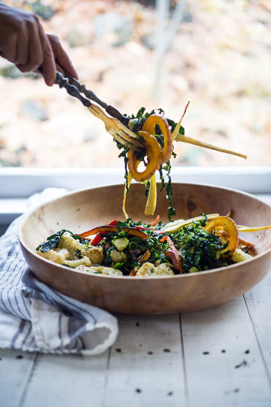 A hearty, healthy Roasted Fall Vegetable Salad with Maple Curry Vinaigrette on a bed of shredded kale and brussel sprouts. Vegan and GF.   www.feastingathome.com