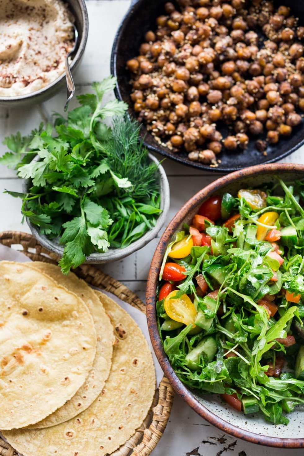 EAT CLEAN with these 20 simple Plant-Based Meals    Middle Eastern Salad Tacos with spiced chickpeas, hummus and a mound of lemony salad, topped with fresh herbs and scallions. Vegan & sooooo Delicious!   www.feastingathome.com