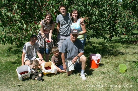 Extended family picking cherries