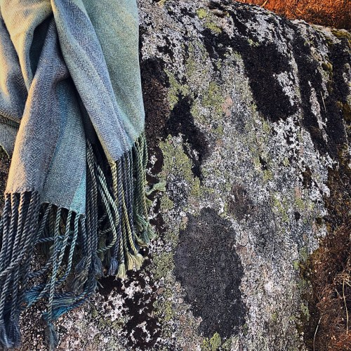 stone blue shawl resting on lichen covered stone