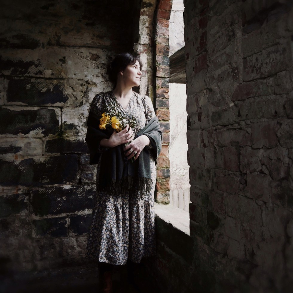 woman in dress looking out of an old building's window. Holding daffodils.