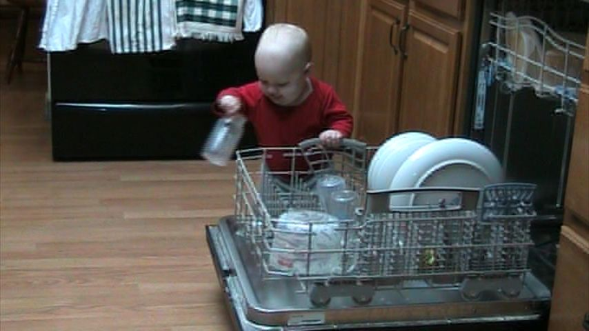 Spencer helps unload the dishwasher