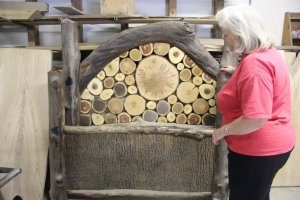 Angie shows off a bed Lewis and Steve made from tree trunks and bark