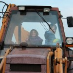Meg and Spencer pretend to drive the tractor