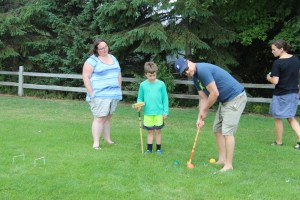 Spencer watches Will hit the croquet ball