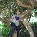 Meg climbing a tree in the park