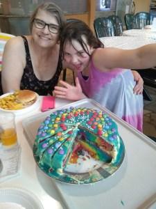 Meg and Grandma showing off the rainbow cake