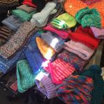 This is an image of donated colourful scarves and beanies