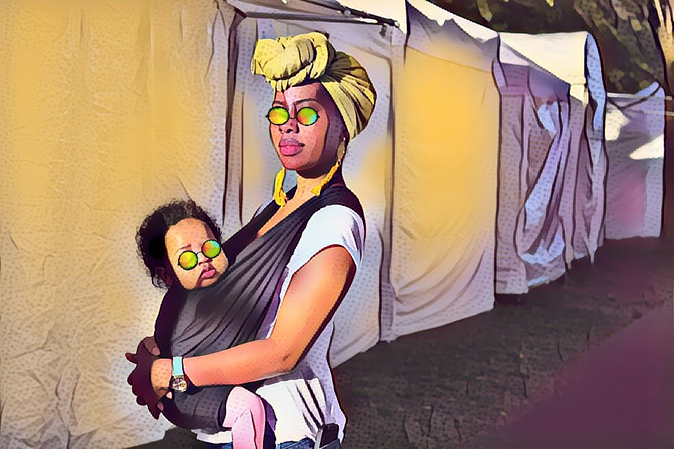 Woman wearing a turban and wearing baby in Baby K'Tan at an art festival
