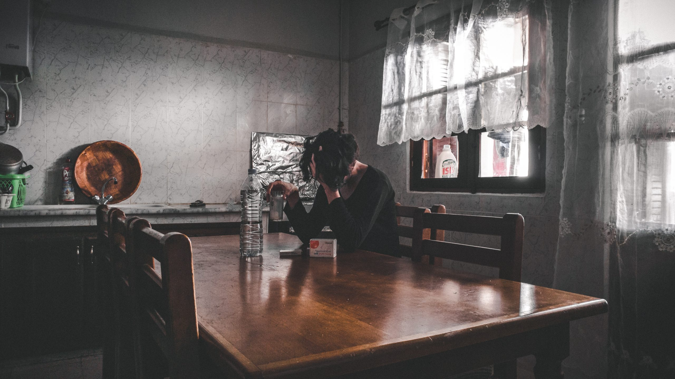 Woman sitting at a table looking sad
