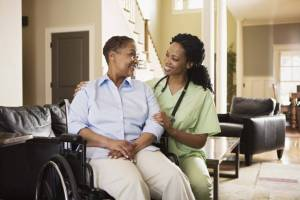 Young caregiver smiling at a woman sitting in a wheelchair