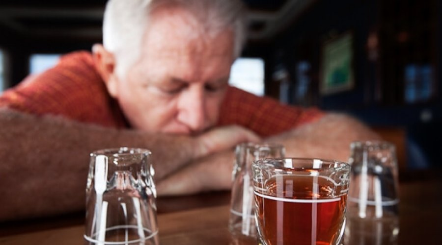 Older man at a bar with his head on his hands
