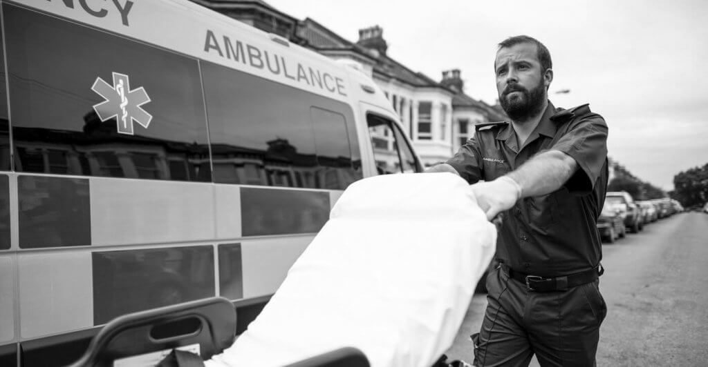 Black and white photo of an ambulance and an EMT