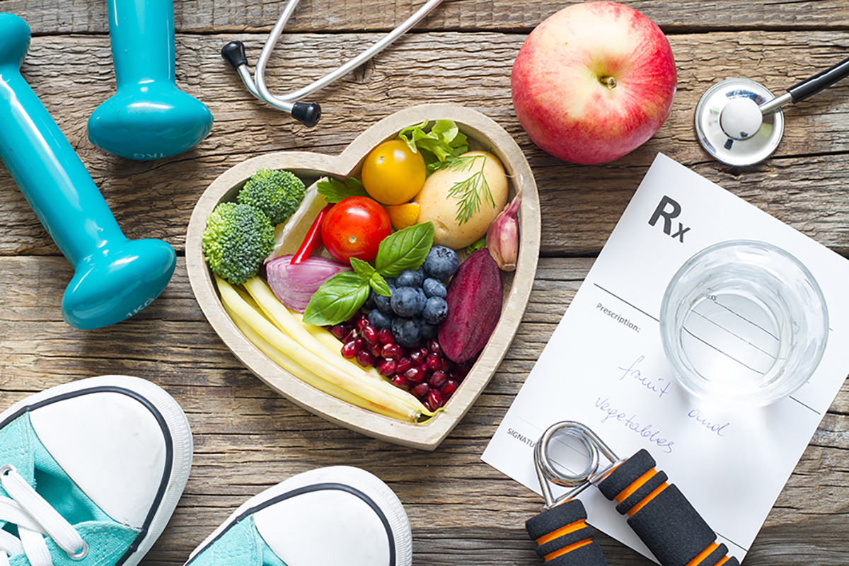 Picture of healthy foods, workout equipment, and a doctor's stethoscope