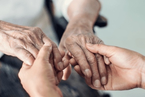 Hands holding an older person's hands while comforting them