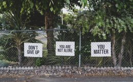 Signs on a fence that say inspirational messages of hope