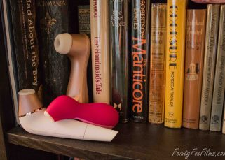 Satisfyer 2 lies on its back on the book shelf, nozzle up. Behind it, the Satisfyer Pro 2 leans against some books, and the Pro Penguin lies nozzle-down across the 2 in the front. The shot is taken on an angle with the toys on the left hand side.