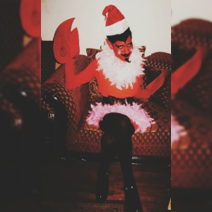A very thin person sits on an oversized, ornate red chair. They are dressed like Him from The Powerpuff Girls; wearing black shiny shoes, black tights, and a short Santa dress that is belted very tightly around their waist. They have a Santa hat on, their face is made up to look like a devil, and they have large red crab-like claws over their hands.