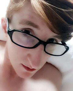 A slightly stoned-looking Taylor peers over their glasses at the camera. Their shoulders are bare and they're lying in a hospital bed.