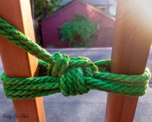Green rope tied in a lark's head double coloum around two bars in a railing. in the distance you can see a large tree in front of a red garage. The railing bars and the rope frame the garage and tree perfectly.