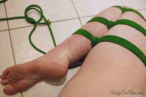 A white leg, bent at the knee and tied tightly with green rope. The rope runs three times down the leg.