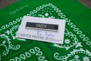 """A pin saying """"Daddy"""" ontop of white cardstock denoting it as being """"for Taylor"""". The carstock sits ontop of a hunter green flagging hanky, the colour for daddies/people wanting daddies"""