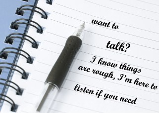 "An open spiral notebook with lined pages and a ballpoint pen. writing in the book says ""want to talk? I know things have been rough, I'm here to listen if you need"""