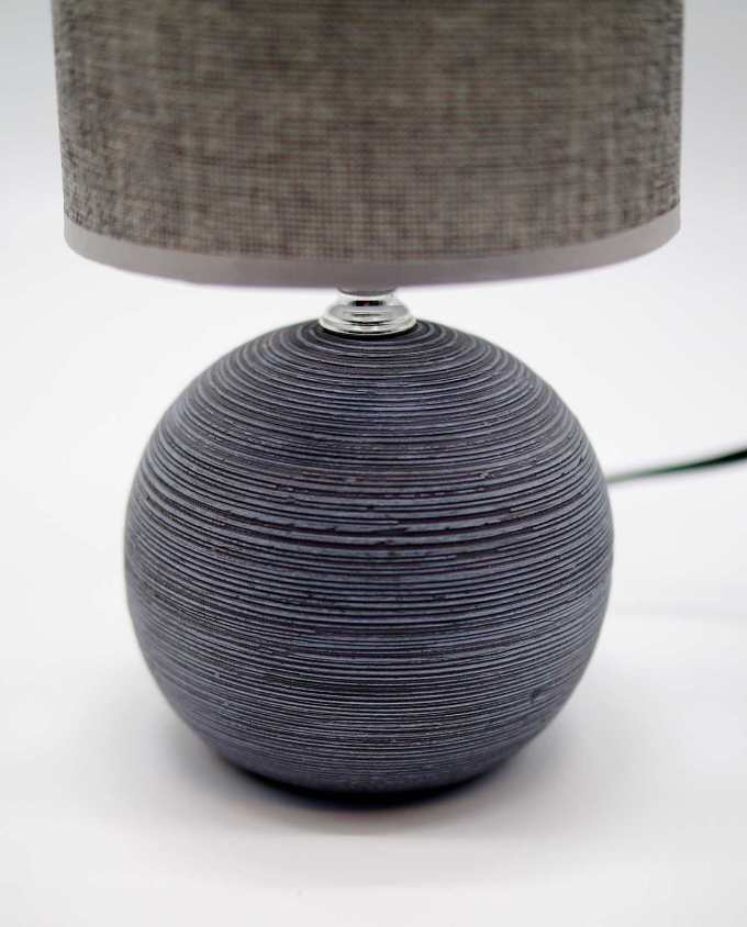A table lamp of round grey ceramic base