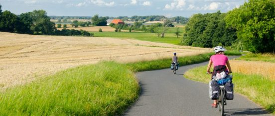 Groupp of cycle tourist on the scenic countryside road in Denmark - island Mon.