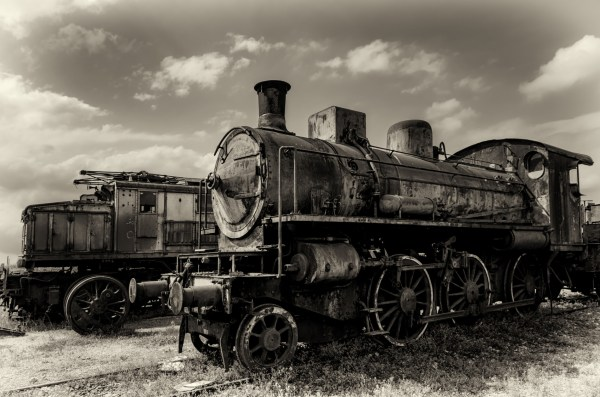 Vintage looking photo of two rusty old talian steam and electric locomotives