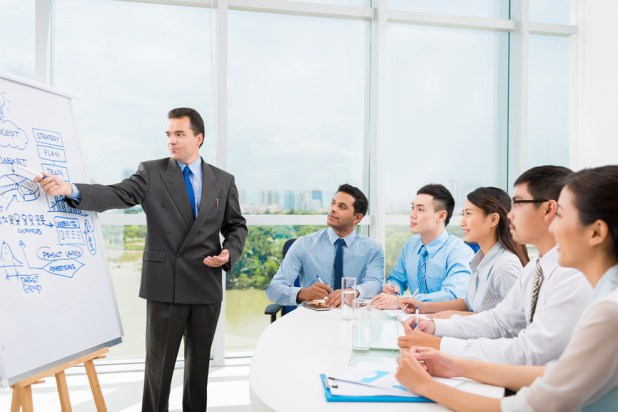 Caucasian businessman conducting training for his multi-ethnic employees