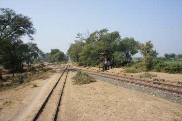 """Eine sogenannte """"Diamond Crossing"""": Eine Breitspurstrecke kreuzt mit einer Schmalspurbahn. Rechts daneben befindet sich in offener Bauweise das Stellwerk (bei Valodara, Gujarat)"""