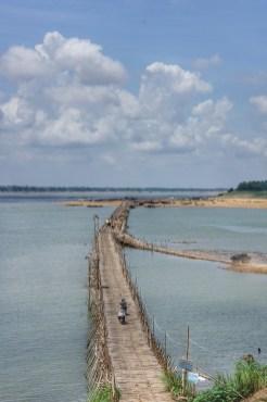 Dieses Bambusbrücke verbindet Kompong Cham mit der Insel Koh Paen und überspannt dabei einen Seitenarm des Mekongs. Wenn die Flusspegel nach der Regenzeit sinken wird die Brücke aufgebaut und einige Monate später, wenn die Regenzeit wieder einsetzt, abgebaut. Jedes Jahr aufs Neue. Während der Regenzeit pendelt ein Fähre. Damit ist jedoch bald Schluss: Einige hundert Meter westlich befindet sich eine feste Brücke im Bau