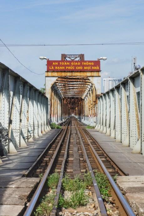 """Ich hätte lieber ein Foto gezeigt, das diese Brücke über den Roten Fluss in Hanoi in ihrer vollen Länge zeigt. Allerdings ist die Brücke zwei Kilometer lang - ein ansprechendes Bild gelang mir nicht. Wie viele strategische Infrastrukturen wurde diese Brücke während des Vietnamkrieges häufig ins Visier genommen und von US-Bombern zerstört. Die Nordvietnamesen schafften es jedoch immer, die Verbindung wieder herzustellen - indem sie für die Reparatur US-amerikanische Kriegsgefangene einsetzte. Irgendwann hatten die US-Amerikaner keine Lust mehr auf dieses """"Spiel"""" und stellten die Bombardierung der Brücke ein. Der Hinweis über der Brücke bedeutet übersetzt etwa: """"Sicherer Verkehr ist Glück für jedes zu Hause"""""""
