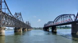 """Dandong ist der wichtigste Grenzübergang zwischen China und Nordkorea. Über die kombinierte Straßen- und Eisenbahnbrücke links im Bild rollen unentwegt Lkw, Busse und Autos - wenn sie nicht von einer Zugfahrt gestoppt werden. Die Brücke rechts im Bild, die von den US-Amerikanern im Korea-Krieg 1950 """"aus Versehen"""" bombardiert wurde (sog. """"Broken Bridge""""), endet kurz hinter der Flussmitte"""