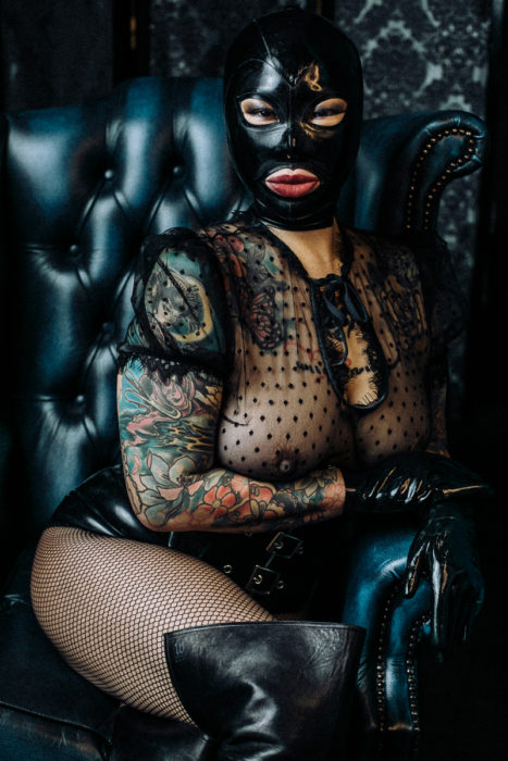 Black latex hood Mistress sitting in leather throne
