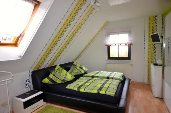 Schlafzimmer mit großem Lederdoppelbett und TV