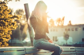 Blond woman in jeans and leather jacket on bench at bus stop in sunset
