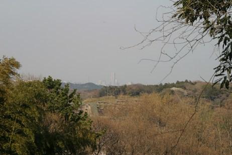 La campagne montagneuse. On aperçoit également la tour Landmark de Yokohama, au loin, qui surgit au milieu de nul part.