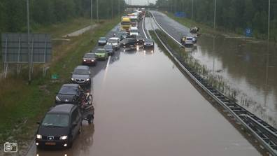 Photo shows standing water on highway preventing motorists from passing and causing a severe traffic jam.