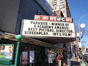 "A black and white marquee celebrating the Oscars win of the movie ""Parasite."""