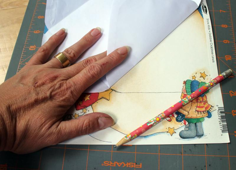 Using the blank envelope as a template, trace the outline on the paper
