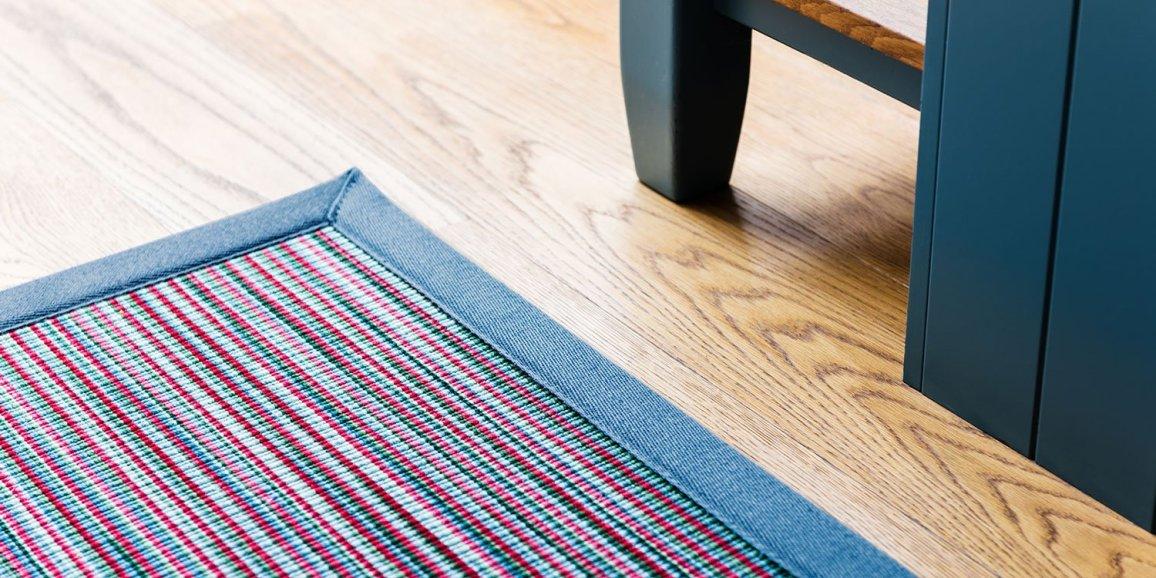 Wool Longitude Antigua rug with Ocean Blue linen border